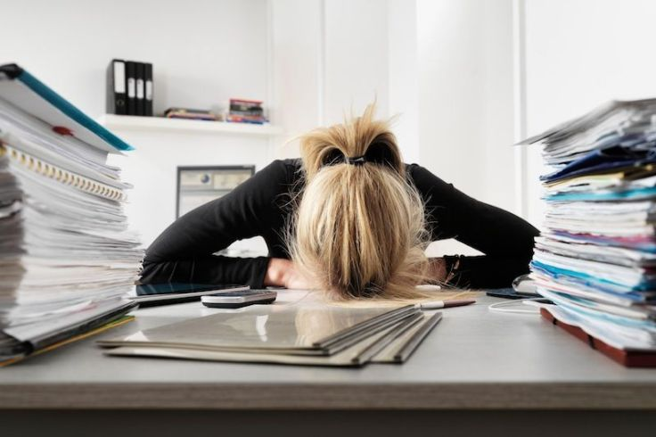 woman-overworked-stressed-paperwork-482184301-jason-butcher-cultura-getty-compressor